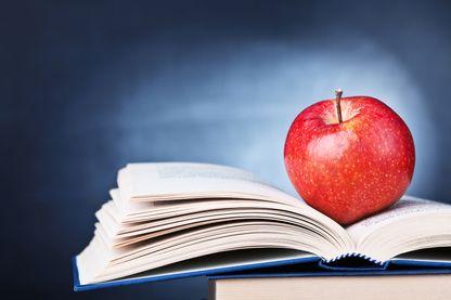 Gros plan d'une pomme sur un livre.