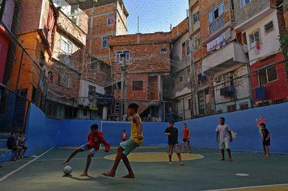 Des enfants jouent au football sur un terrain de la favela Tavares Bastos à Rio de Janeiro, au Brésil, le 27 mai 2018.