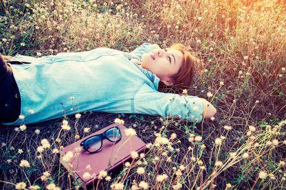 Une femme immobile sur l'herbe.
