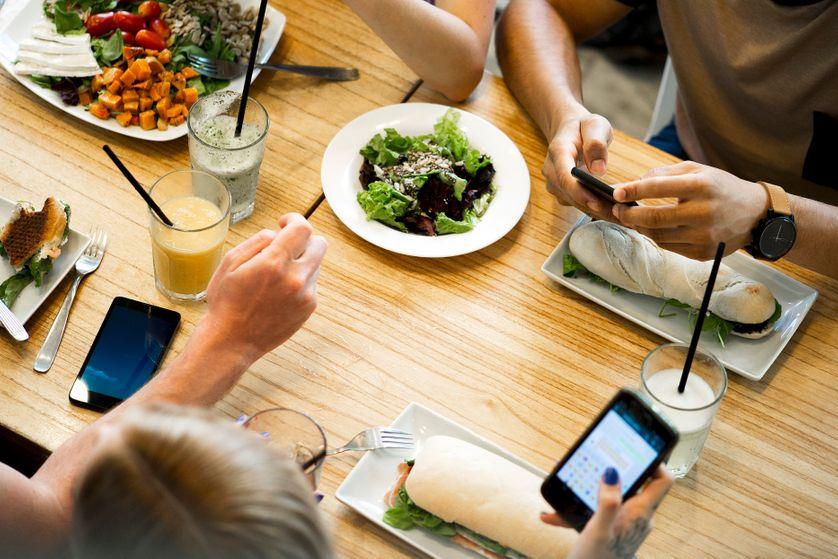 Des personnes utilisent leur smartphone pendant un repas