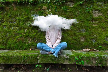 Femme jeune avec la tête assise sur un banc avec la tête entourée d'un nuage