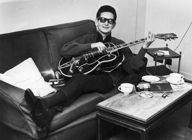 """C'est à Roy Orbison, l'un des pionniers du rock & roll, que l'on doit le tube """"Oh, Pretty Woman"""" en 1964. Il pose ici avec sa guitare dans sa chambre au Westbury Hotel de Londres, le 10 octobre 1964."""