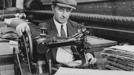 A male factory machinist at work using a Singer sewing machine