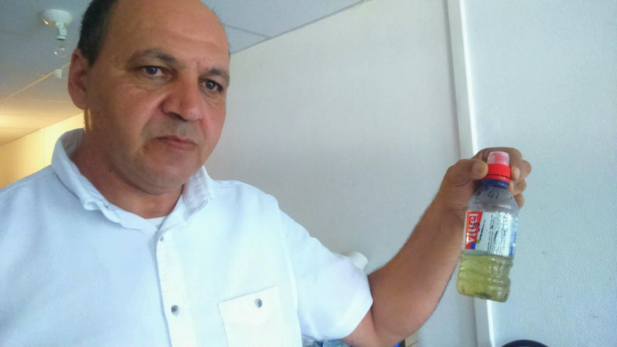 Kader,  membre de l'Amicale des locataires, tenant un échantillon d'eau du robinet.