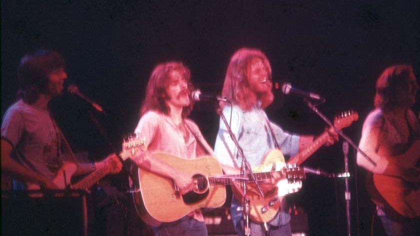 Eagles sur scène, cheveux longs et moustaches sous les projecteurs.