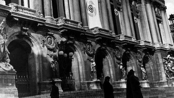 Février 1941. Des drapeaux nazis accrochés à la façade du Palais Garnier (Paris).