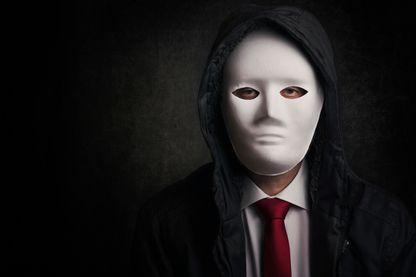 Portrait d'un homme portant un masque sur fond noir.