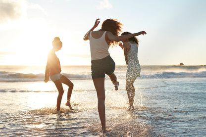 C'est l'été, des jeunes femmes se retrouvent à la plage, au coucher du soleil pour danser.