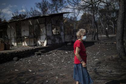 Une femme portant un masque marche devant sa maison brûlée suite à un incendie de forêt dans le village de Neos Voutzas, près d'Athènes, le 26 juillet 2018.