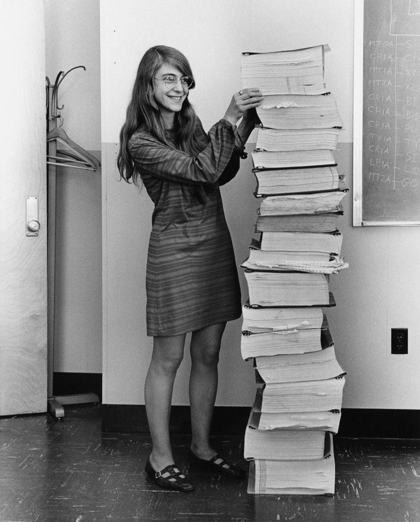 Margaret Hamilton se tenant auprès du code du logiciel de navigation qu'elle et son équipe ont produit pour le programme Apollo.