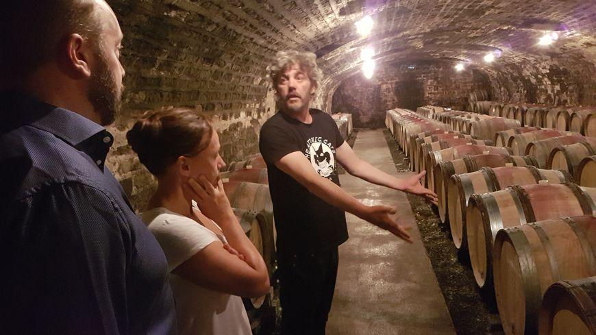 Devant des touristes suédois, François Leclerc explique les secrets de fabrication du vin de son domaine à Gevrey-Chambertin, lors de la visite de sa cave.