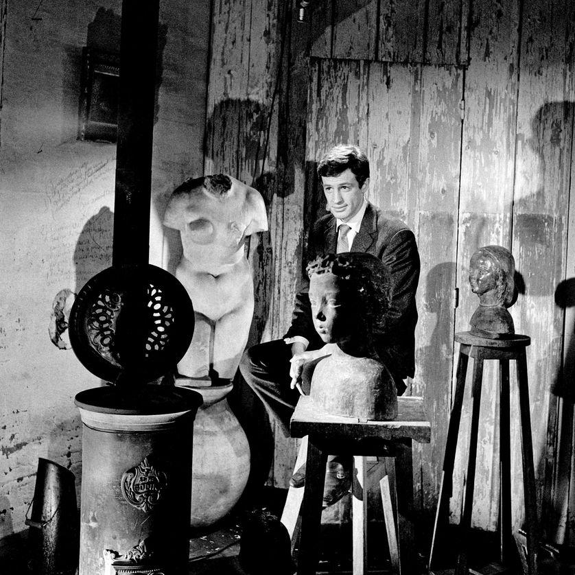 """Jean-Paul Belmondo entouré de sculptures de son père Paul Belmondo, pour l'émission """"Cinépanorama"""" le 20 janvier 1960."""