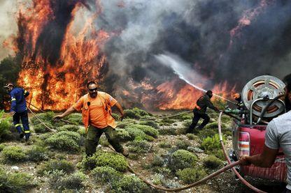 Près d'Athènes, dans le village de Kineta, pompiers et volontaires tentent de combattre le feu