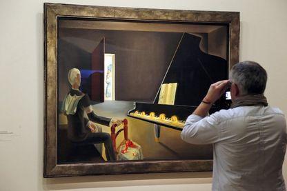 """Un visiteur regarde un tableau intitulé """"Hallucination partielle, Six images de Lénine sur un piano"""", 1931, de Salvador Dali pendant une exposition consacrée à son travail à Beaubourg, Centre Pompidou, le 19 novembre 2012 à Paris."""