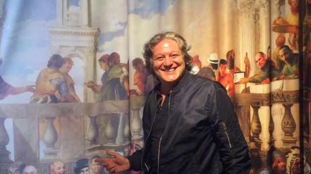 Cédric Naimi, auteur et fondateur de l'association Graffart, posant devant un rideau du MOB Hôtel