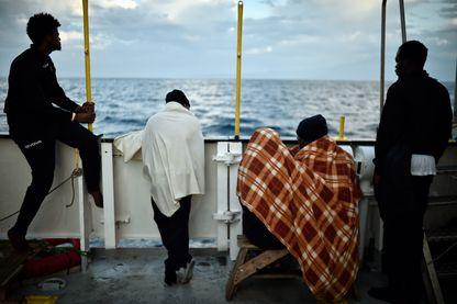 Des migrants regardent le littoral après leur sauvetage par l'Aquarius, au large de la Sicile, le 14 mai 2018
