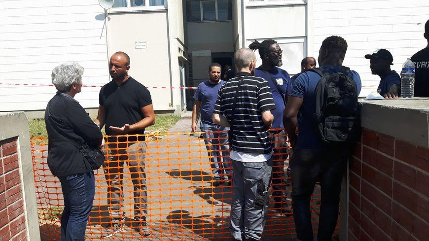 A l'entrée de l'immeuble, toujours bouclé, les habitants viennent demander des informations