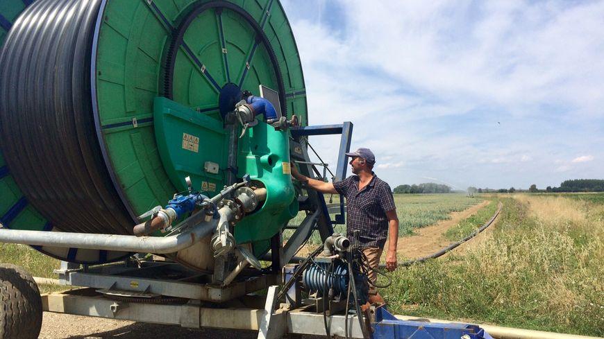 Jean-Michel Fèvre, le président de l'ASA de la Biètre et l'enrouleur qu'il lui permet d'irriguer ses pommes de terre depuis le bassin