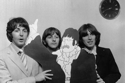 Paul McCartney, Ringo Starr et George Harrison avec un cartoon de John Lennon.
