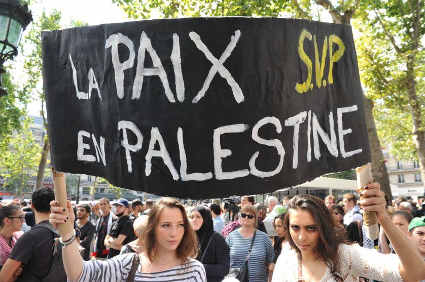"""Deux manifestantes portent une banderole au nom de """"La paix en Palestine, svp"""", à Paris Place de la République le 26 juillet 2014 en soutien à la Palestine."""