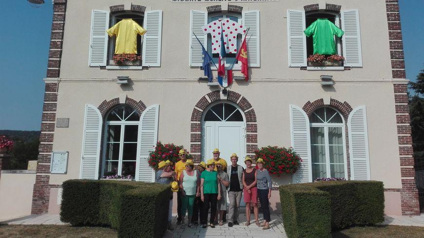 Une partie des  bénévoles pose devant la mairie de Bueil, où ont été accrochés trois maillots XXXXXL, cousus main !