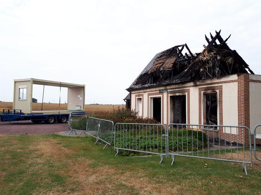 A droite, la mairie incendiée, à gauche, l'un des bungalow de remplacement.