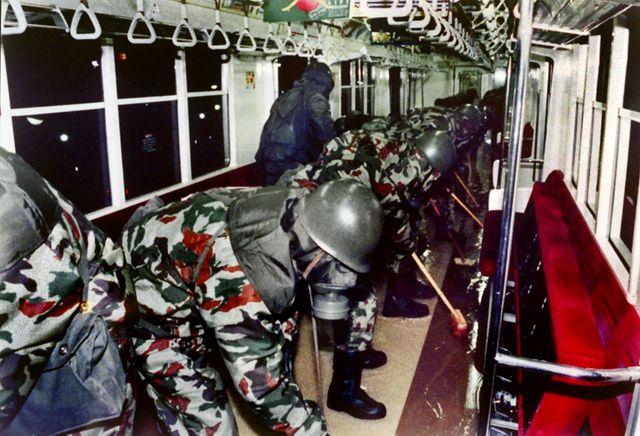 Des militaires japonnais, équipés de masques à gaz, nettoient une rame du métro de Tokyo, après l'attaque au gaz sarin de 1995.