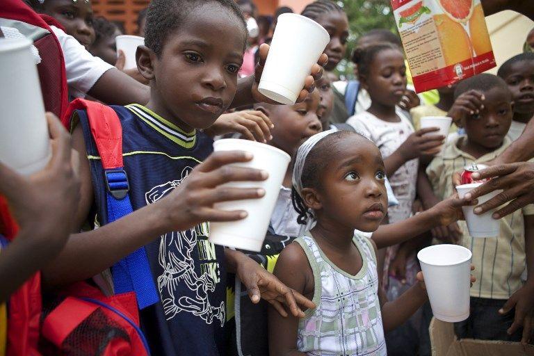 """Des enfants de l'école de Tabarre boivent, le 25 septembre 2010 à Port-au-Prince, lors d'une livraison de fournitures scolaires dans le cadre de l'opération """"Un cartable pour Haïti""""."""