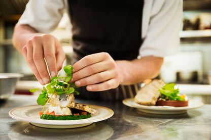 Gros plan d'un Chef dans sa cuisine ajoutant une garniture de salade à une assiette de poisson grillé.