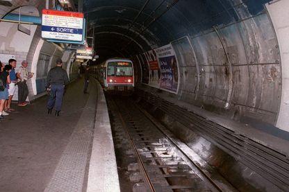 Des policiers regardent un RER entrer dans la station Saint-Michel où les traces de l'attentat à la bombe sont encore visibles sur les murs, le 26 juillet à Paris, au lendemain de l'explosion revendiquée par le GIA.