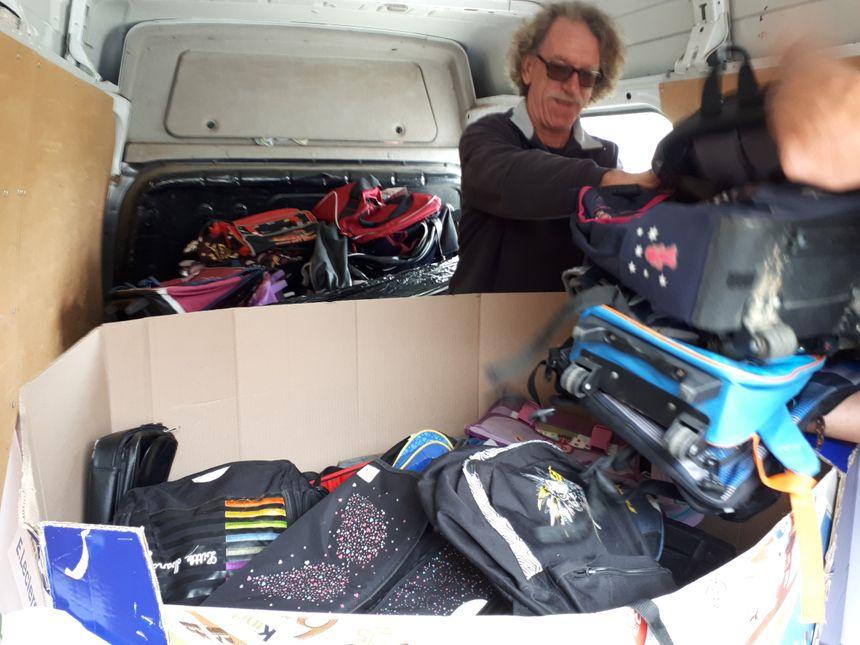 Une camionnette du Secours populaire remplie de sacs à dos et cartables neufs
