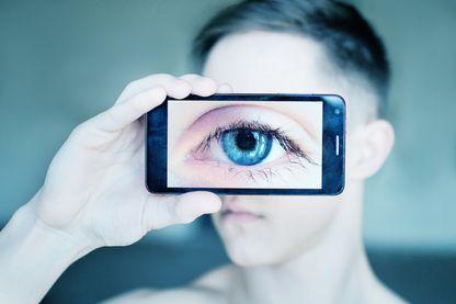 Gros plan d'un œil humain à travers un téléphone portable.