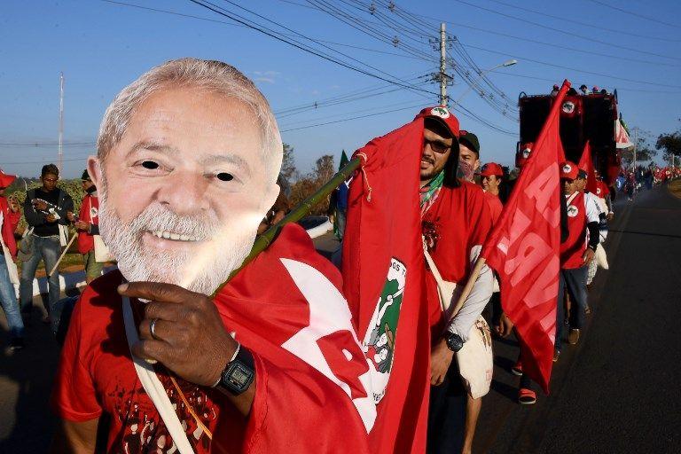 """Les membres du Mouvement des paysans sans terre portant des masques de l'ancien président brésilien Luiz Inacio Lula da Silva, participent à la marche """"Free Lula"""" près de Brasilia, le 14 août 2018."""
