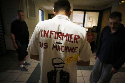 Une infirmière porte une blouse blanche ornée d'un slogan qui se traduit par «Je suis une infirmière, pas une machine», marche dans un hôpital psychiatrique surpeuplé.