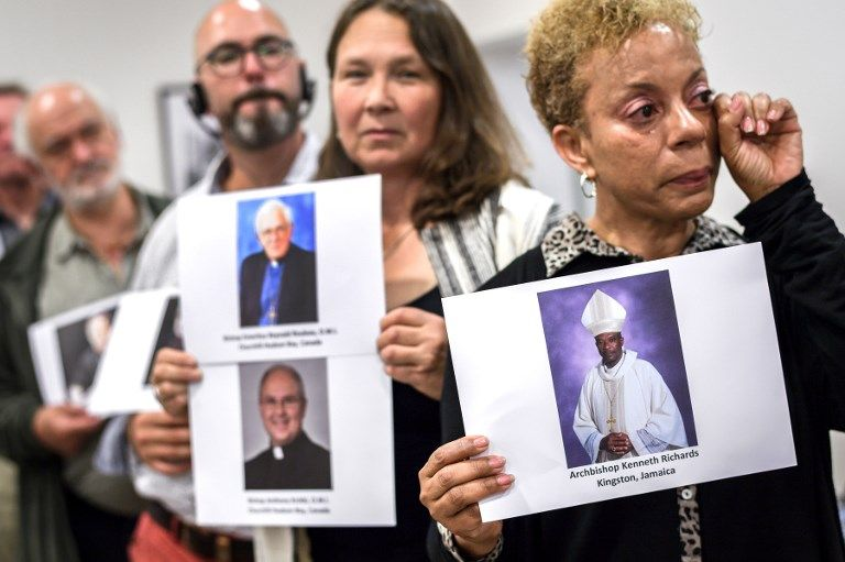 Des militants de Ending Clergy Abuse (ECA), une organisation internationale contre les abus sexuels d'enfants dans l'Église catholique posent avec des photos de membres du clergé.