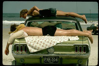 Trois jeunes qui bronzent en écoutant la radio sur une Ford Mustang de 1967 ? Quoi de plus normal sur la plage de Daytona Beach dans les années 70