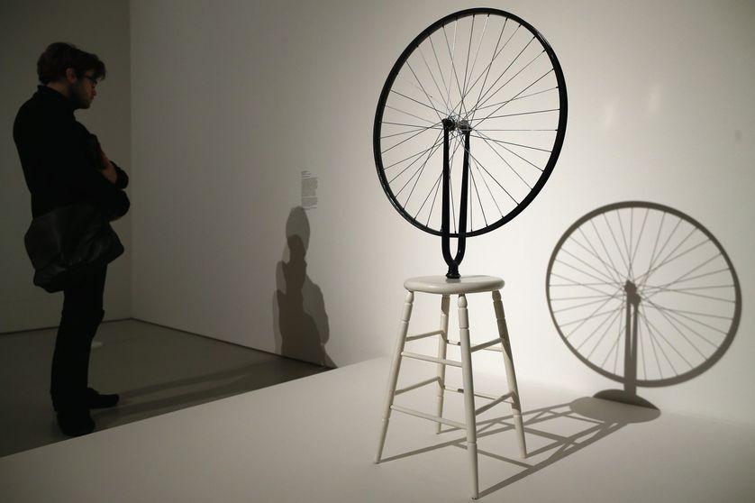 """Un visiteur devant le ready-made """"Roue de bicyclette"""" de Marcel Duchamp lors d'une exposition à la Galerie Barbican à Londres en février 2013."""
