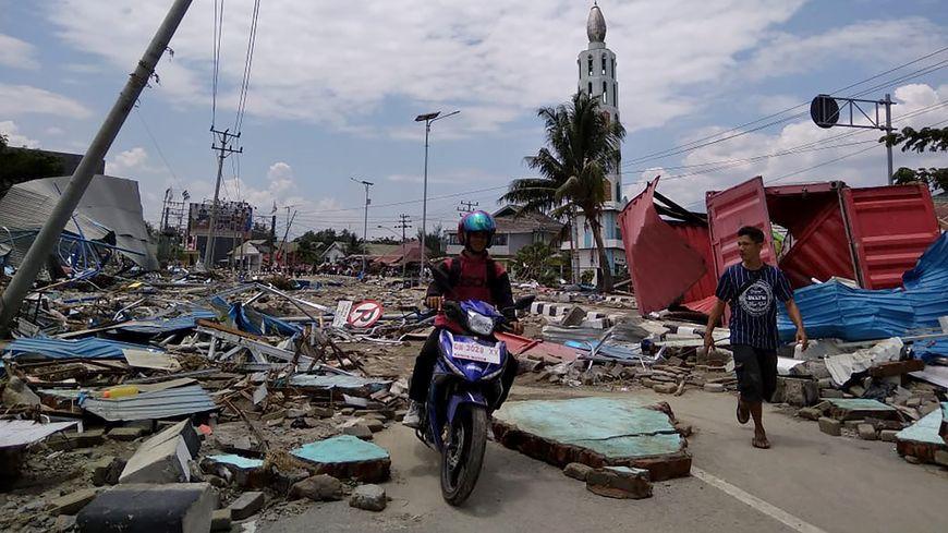 Des habitants se déplacent dans une rue pleine de débris après le tremblement de terre et le tsunami qui ont frappé Palu.