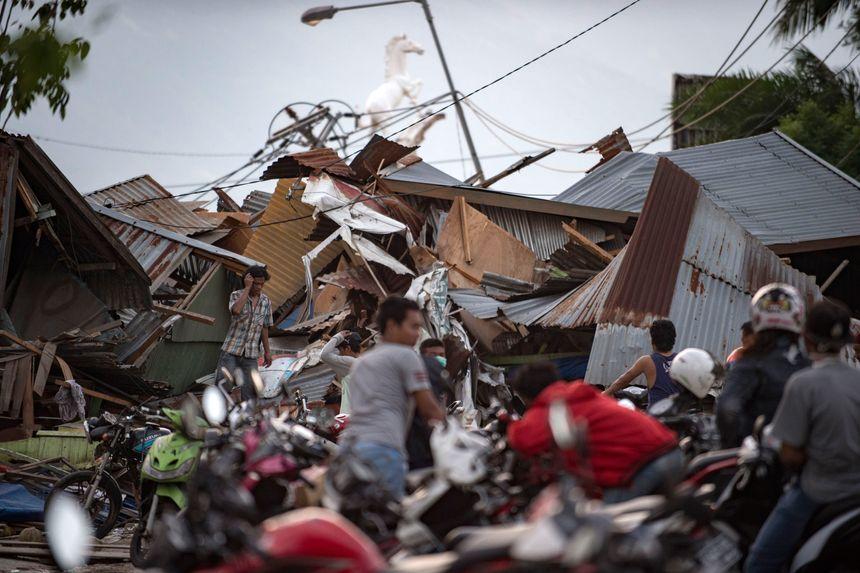 Des habitants recherchent leurs biens parmi les débris de maisons détruites. - AFP