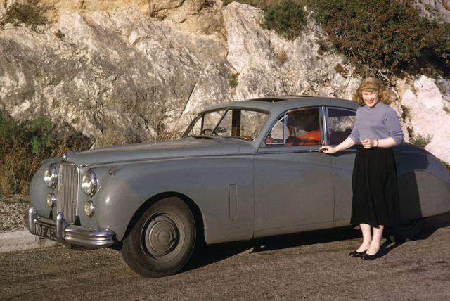 Roberta Cowell pose à côté de sa Jaguar Mark VII dans le sud de la France en avril 1954