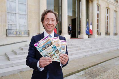 Stéphane Bern pose avec des billets de loterie pour la loterie 'Loto du patrimoine', qui vise à aider à la restauration des monuments menacés, à l'Elysée à Paris le 31 mai 2018.