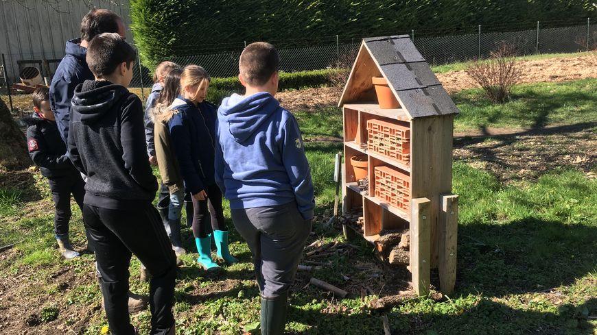 Quelques enfants de l'école des Planches à St Maur devant un hôtel à insectes dans leur jardin pédagogique