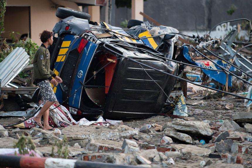 Un jeune dans une rue éventrée par le tsunami. - AFP