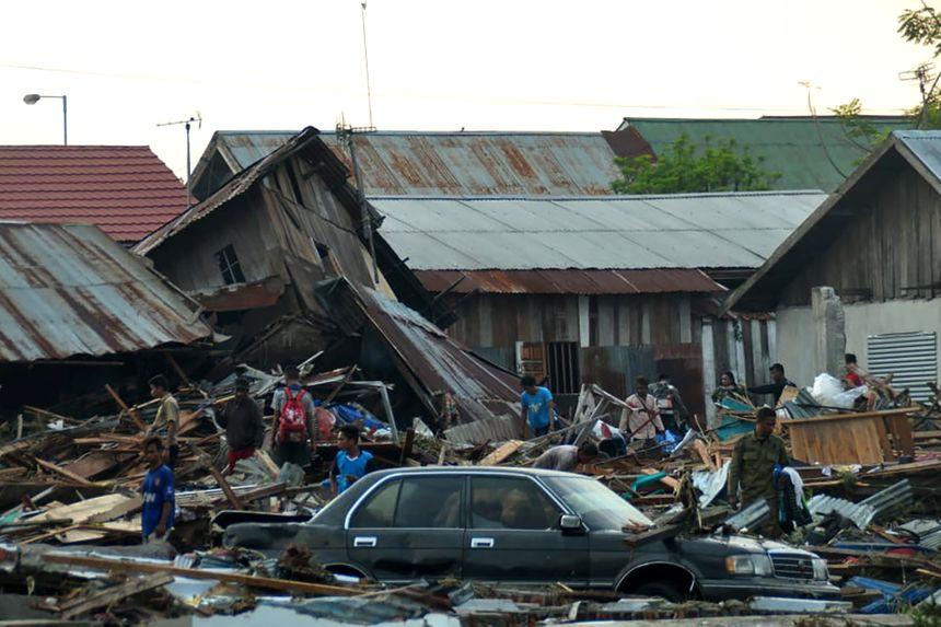 Des résidents tentent de récupérer des affaires personnelles dans leurs maisons effondrées. - AFP