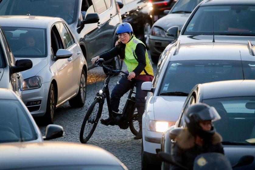 Une cycliste dans les embouteillage à Paris place de la Concorde
