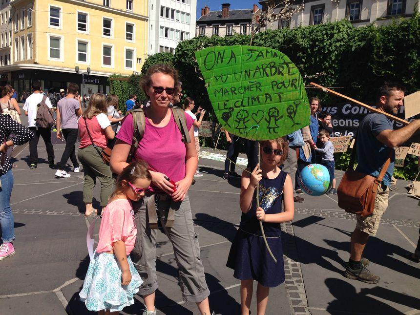 """Aude et ses filles avec leurs pancartes """"faites maison"""""""