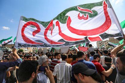 Des Syriens de la ville d'Idlib et des villes environnantes, agitent une bannière aux couleurs de l'opposition pendant une manifestation anti-gouvernementale sur une place principale à Idlib le 14 septembre 2018.