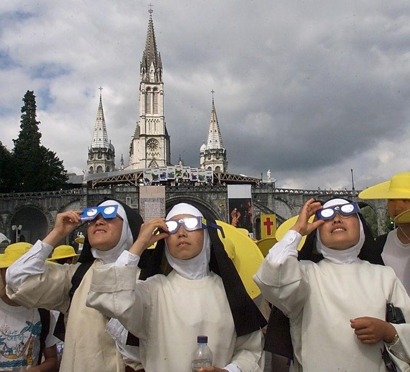 Des bonnes soeurs péruviennes en pèlerinage à Lourdes regardent la dernière éclipse du soleil du millénaire sur le continent européen, depuis le parvis de Notre Dame de Lourdes, le 11 août 1999.