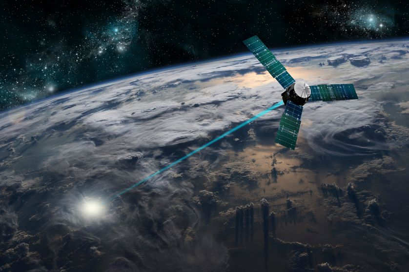 A composite image of a satellite firing an energy weapon at a target on Earth.