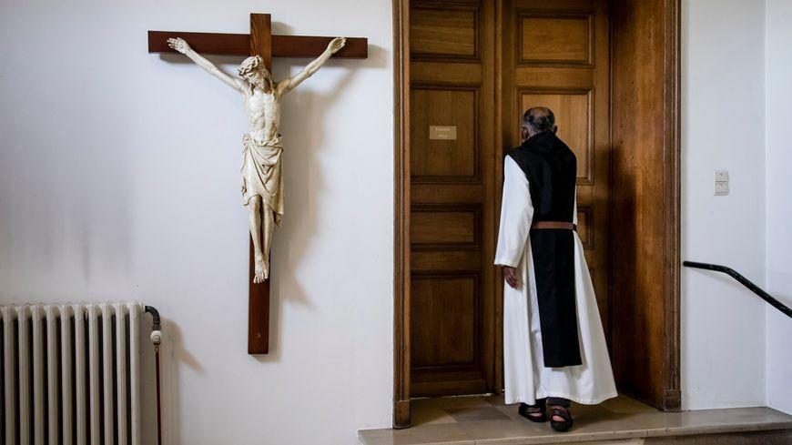 Une croix et un moine de dos (photo d'illustration).